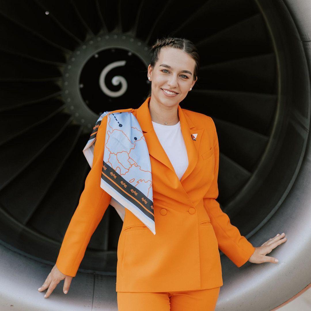 SkyUp. В 2021 году украинская авиакомпания представила новую форму: оранжевый брючный костюм с шелковым платком и удобные кроссовки.